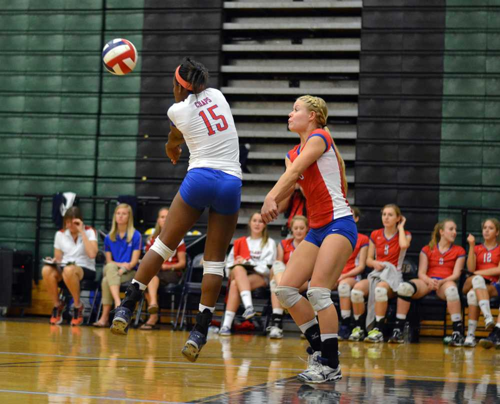 Libero junior Sydney Fowler jumps in front of senior Megan Mellenbruch to make a pass at the game at Akins on Sept. 17.
