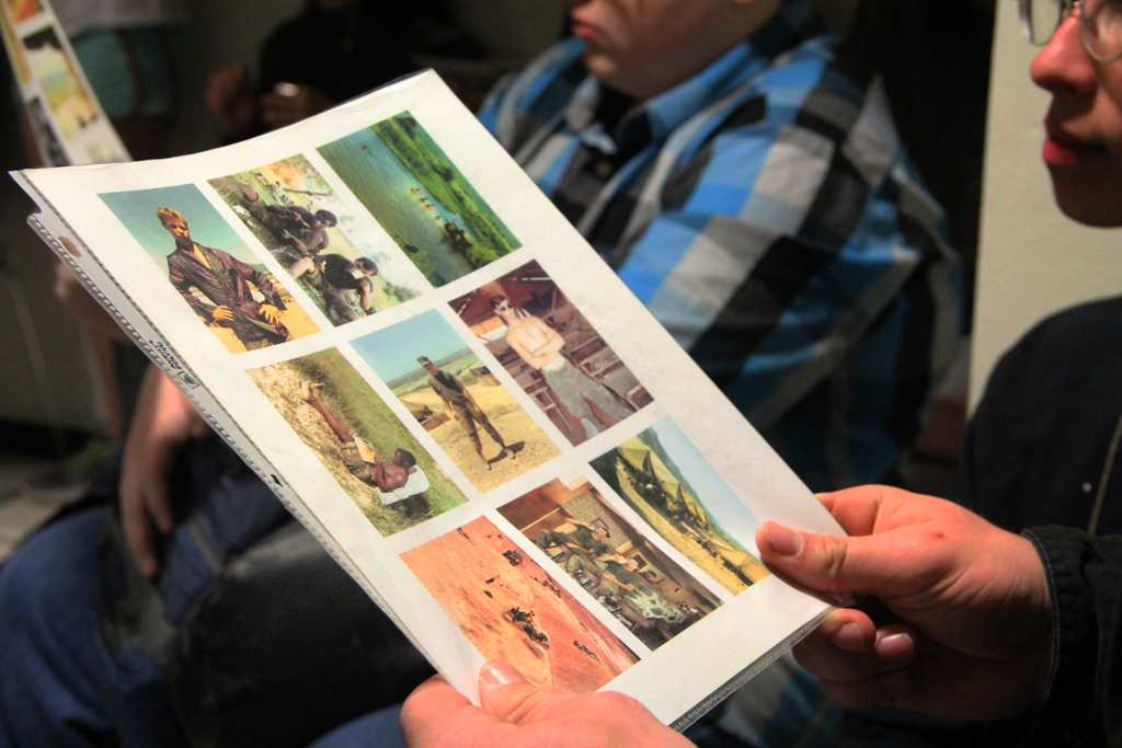 Student examines a collage of photos from the Vietnam war while the war veterans speak about their experiences.