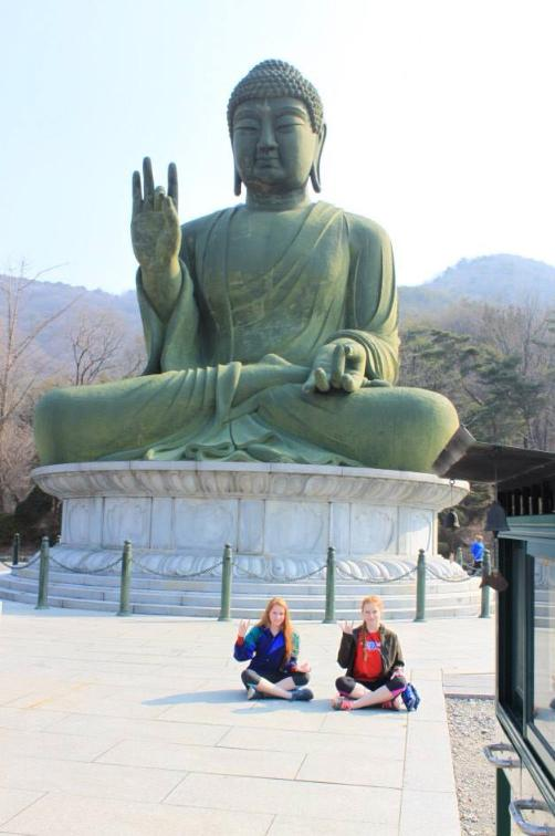 Westlake+juniors+Sarah+Tucker+and+Hannah+Tucker+sit+in+front+of+a+statue+at+a+Buddhist+temple.