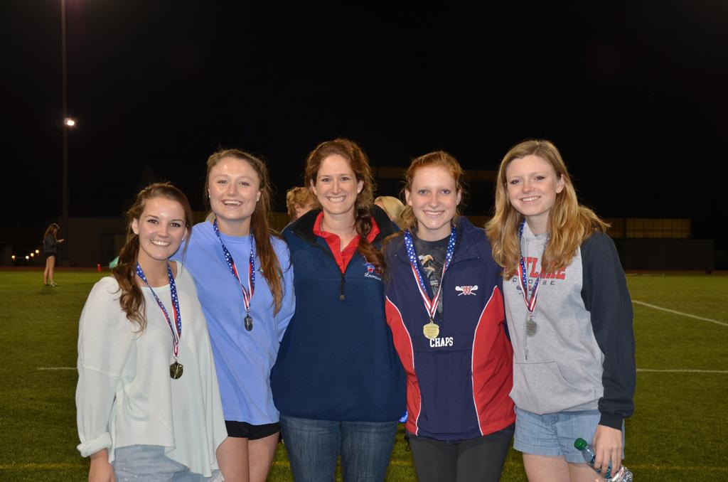 Girls lacrosse player pose for a picture with their medals after the District awards. From left: Juniors Annie Flowers, Harper Young, Coach Lauren Fitzgerald, junior Sarah Tucker and senior Sarah Thompson. Not pictured: Zoe Solis
