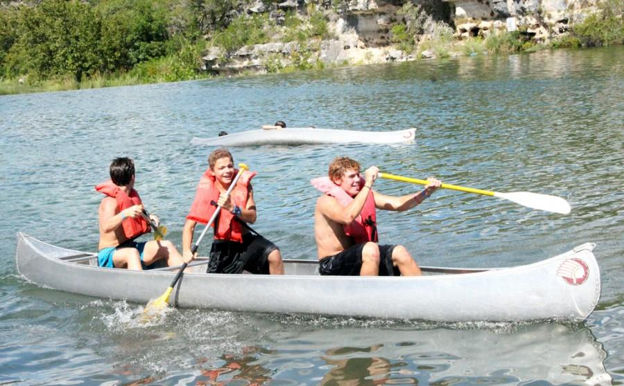 Juniors Nick Carlson and Jule Russel along with Freshman Kevin (last name) laugh as their feelow competetors' canoe tips over in a rowing contest durning the anual Westlake Choir's Mo Lympics located at Mo Ranch on Sept. 6, 2014