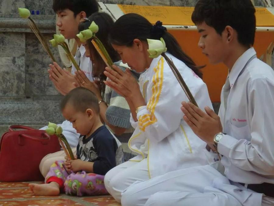 A family prays in a Buddhist temple in Chang Mae, Thailand.