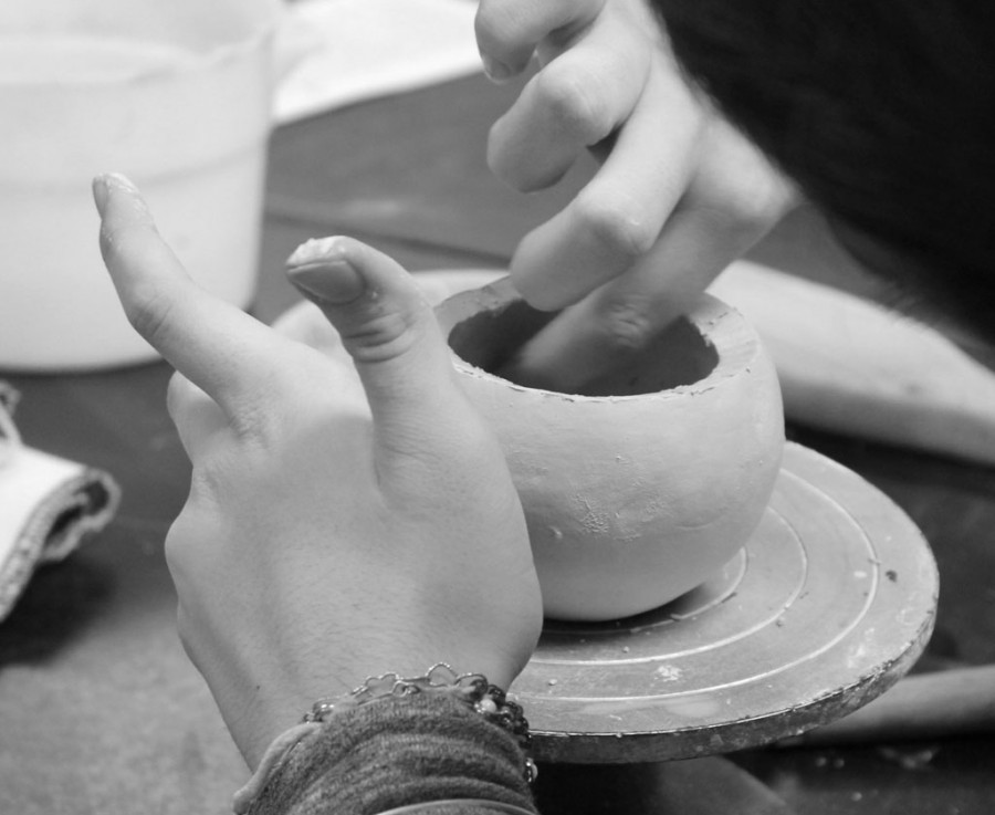A student in ceramics uses a sponge to smooth out any dents or sharp edges on her clay pot.