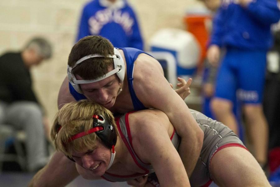Positioning himself above his opponent, senior Alex Pankhurst attempts to push his opponent out of the ring.