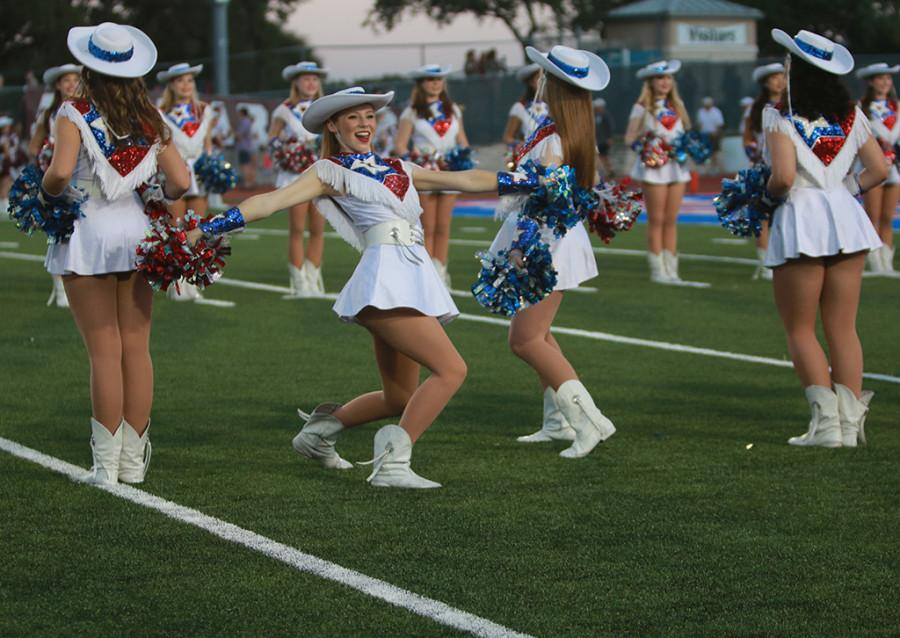 Senior Taylor Champlin turns to face the crowd while cheering on the football team at the Homecoming Game on Sept. 18th.