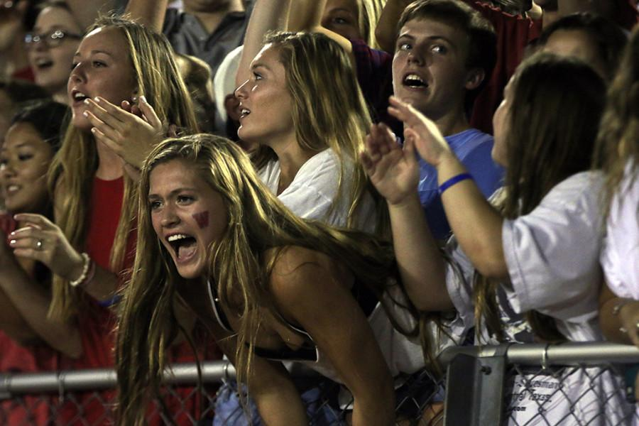Senior Bailey Holle yells at the football game from the student section of the stands.