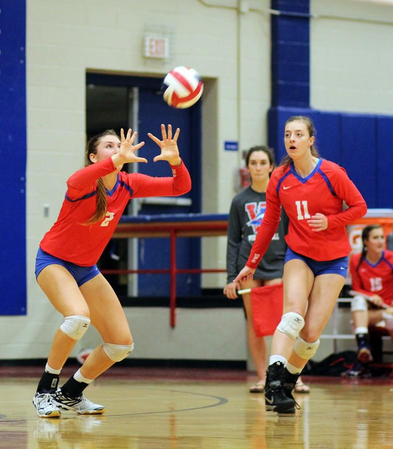 Varsity volleyball team members senior Carly Turner and junior Jessica Schwenke work together to beat their opponent during the teams game against Lake Travis on Oct. 23.