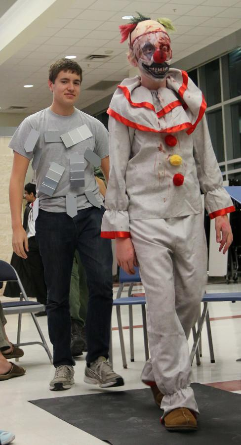 Senior Ben Gorr and freshman Sam Cardiganer presents their costumes during the Holloween orchestra concert on Oct.26.