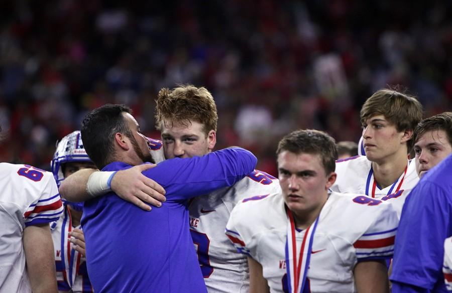 Senior Kody Allen finds comfort in his coach after the Chaps' defeat at the hands of North Shore for the State title.