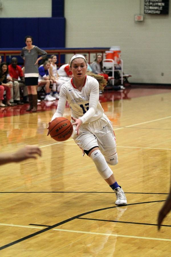 Senior varsity player Brooke Holle dribbles the ball to the three point line to start a play against Hays on Friday Jan. 29. The Chaps won 57-41, securing second place in district.