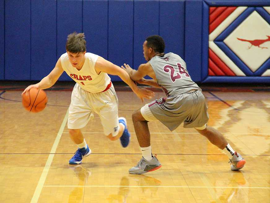 Westlake varsity player sweaps around his Austin High apponent, in search of a path to the basket.  by jake breedlove