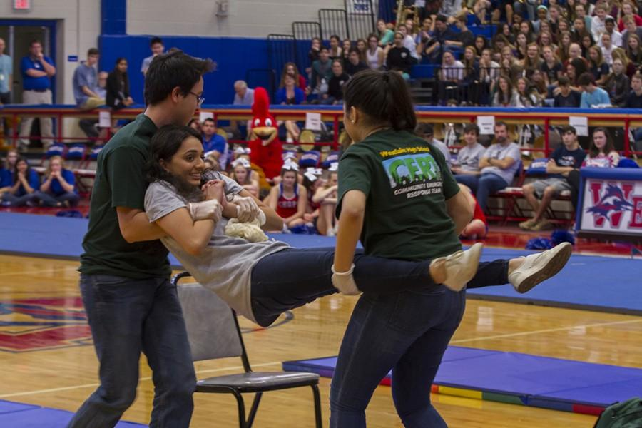 Seniors Johnathan Bunt and Sonya Bakali carry senior Uzmai Momin during a demonstration of CERT competitions.