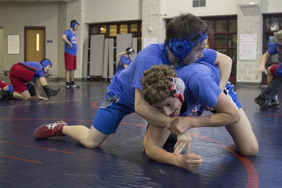 Sophomore Liam Zia wrestles Junior Wyatt Arhens to the ground during practice.