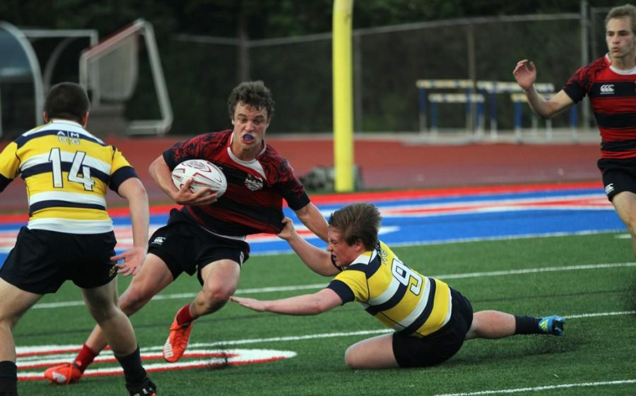 Senior rugby player Ryan Reese recieves the ball and sprints towards his try zone during a game against a Ohio team on March 30.