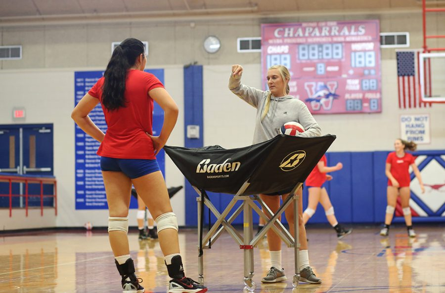 Senior Kassy Doering gets advice from one of the team coaches during a varsity team practice on Aug. 29.