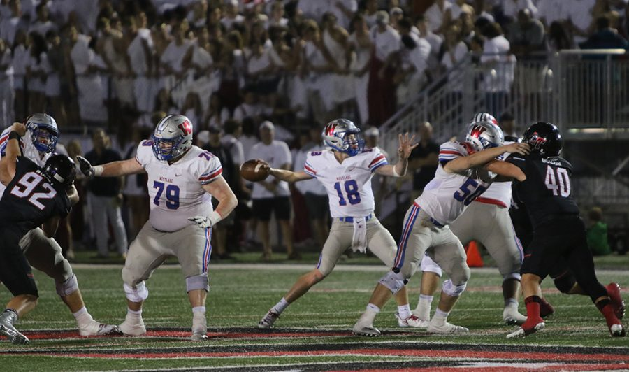 Sophomore Taylor Anderson prepares a pass to Andrew Boykin while Seniors Gray Griffin and Bobby Magee hold off the Lake Travis Defense. Taylor scored Westlake's first touchdown in the fourth quarter, bringing Westlake's score to 7-49.