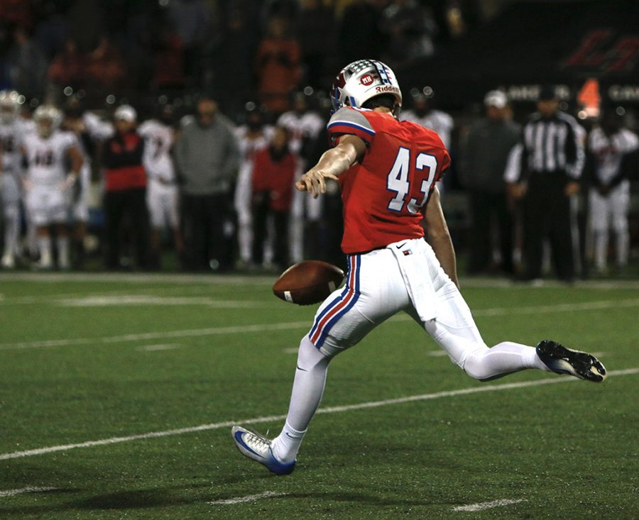 Senior Mauro Montemayor punts the ball to the returning on the fourth down during the Lake Travis football game on Dec 2.