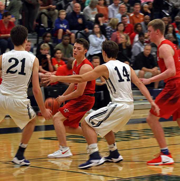 Junior Luke Pluymen being blocked during a charge down the court