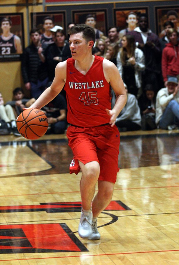 Junior Luke Pluymen brings the ball down the court and sets up the play.