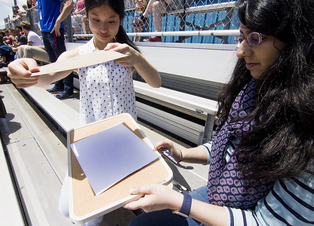 Juniors Helen He and Maha Ikram break out a homemade camera obscura to view the 2017 solar eclipse.
