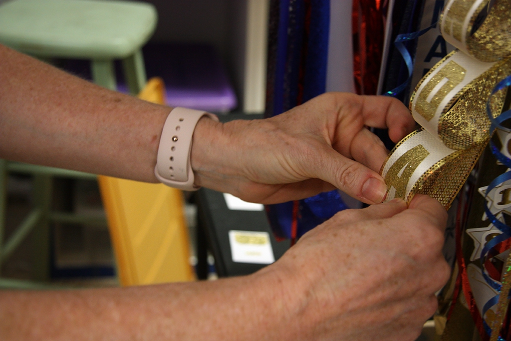 A mom sticks a letter onto a ribbon on a nearly finished mum, just over a week before Homecoming.