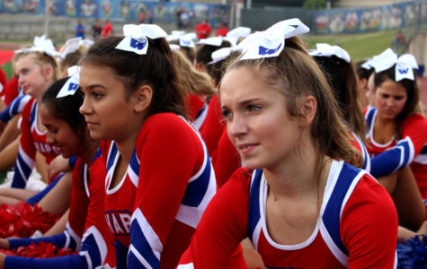 Freshmen Caroline Comeaux and Abby Williamson are sitting on the sidelines of the field, watching the mascots' skit at the homecoming pep rally. Both girls are members of Cheer, and are waiting in between performances. Watching Chips and Queso was a good way to take a break from their tiring routines.