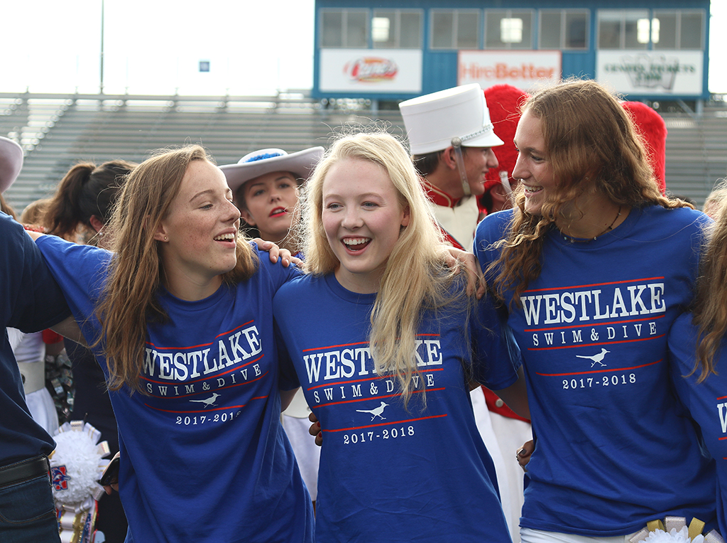 Swim team members seniors Madeline Menefee, Amber Schriever and Morgan Johnson sway and sing along to the alma mater at the homecoming pep rally Sept. 22.