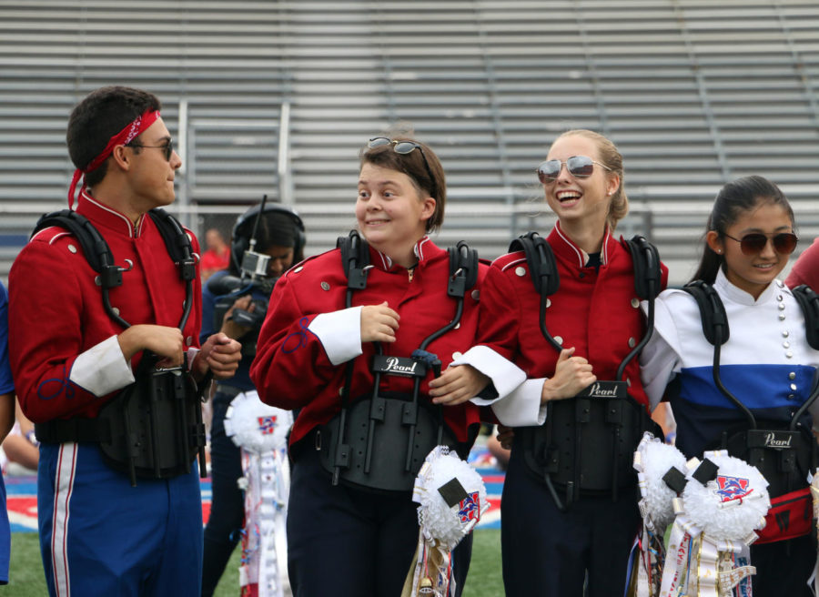 Seniors Marek Monsivais, Leah Holt, Terra Jackson and Grace Li share a laugh while standing in front of the student body during the Homecoming pep rally.
