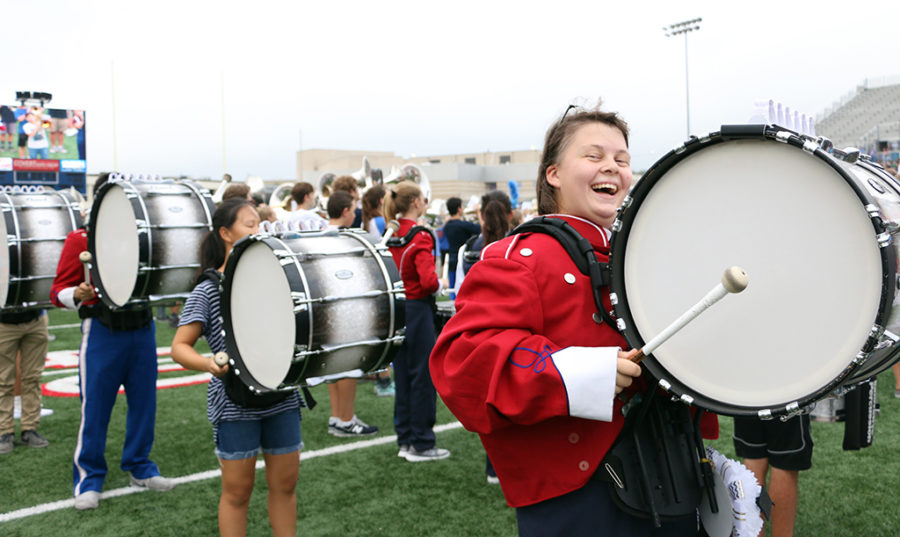 Senior Leah Holt laughs while keeping a beat for the band during the pep rally on Sept. 22.