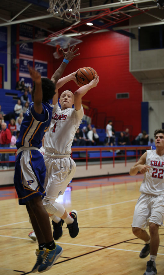 After stealing the ball, sophomore Rory Munro shoots over a Pflugerville player during the game on Dec. 5.