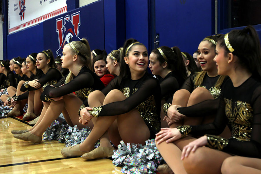 Junior Jenny Chafizadeh sits on the sidlines of the gym with the rest of Westlake Hyline. They are watching the Color Guard's performance at last Thursday's pep rally.