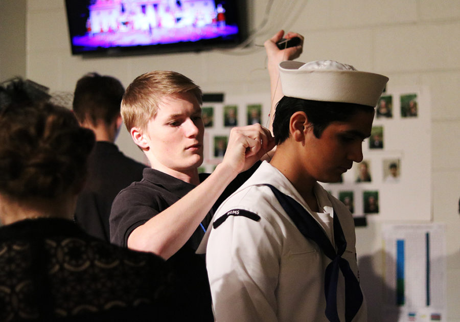 Backstage of this year's musical, Anything Goes, TEC member senior Sean Wangnick removes a mic from a sophomore sailor.