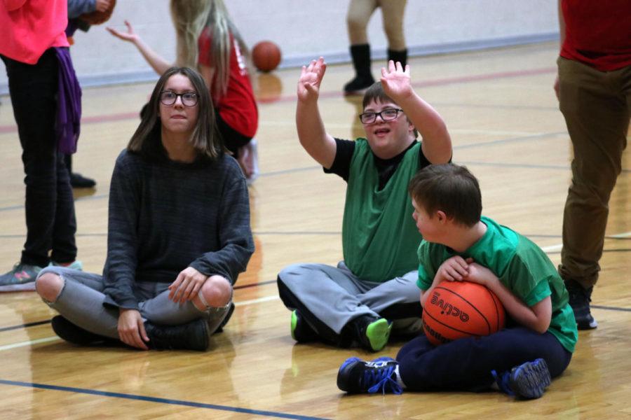 Volunteer Sophomore Michelle Van Dooom, Jackson Henderson, and Ryan Trammell take a quick break to watch others play basketball.