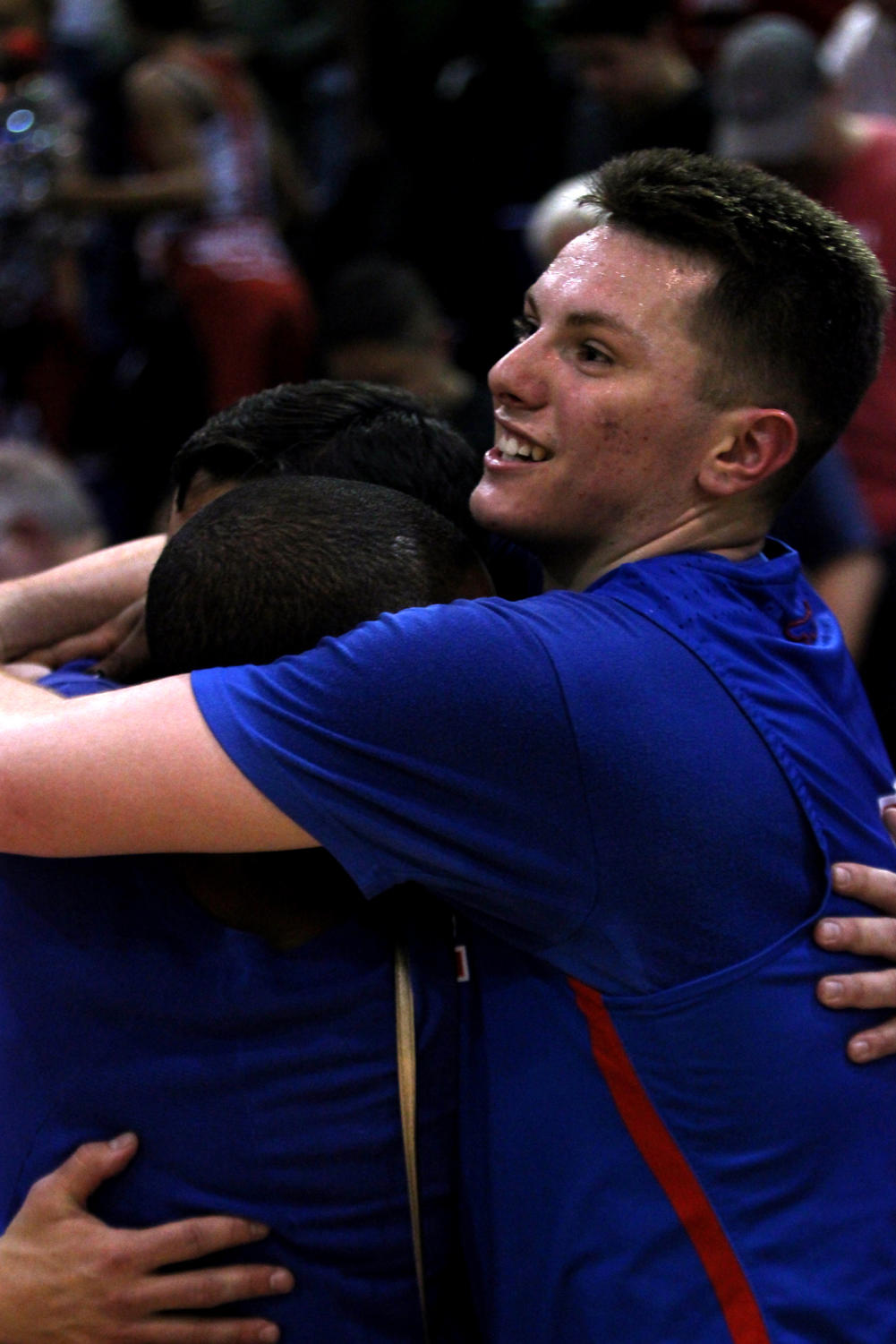 Senior Point Guard Luke Pluymen hugs his teammates to celebrate the 58-57 win against Wagner High School.