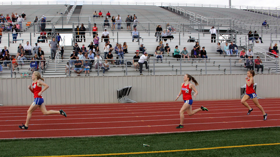 Freshman Elina Mettala, senior Lily Howe, and sophomore Elise Smoot sprint in the last 100 meters of the varsity 800 race at the District meet.