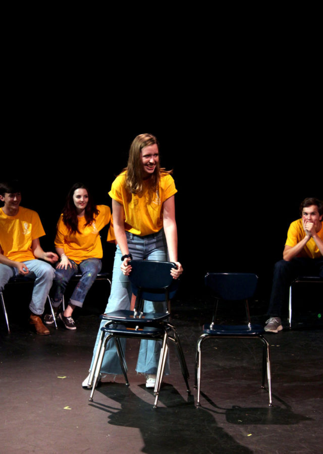 Junior Elizabeth Jackson laughs during her performance at the WIT show. She hints at her addiction to stacking chairs, which was suggested by the audience, during a game of Party Quirks.