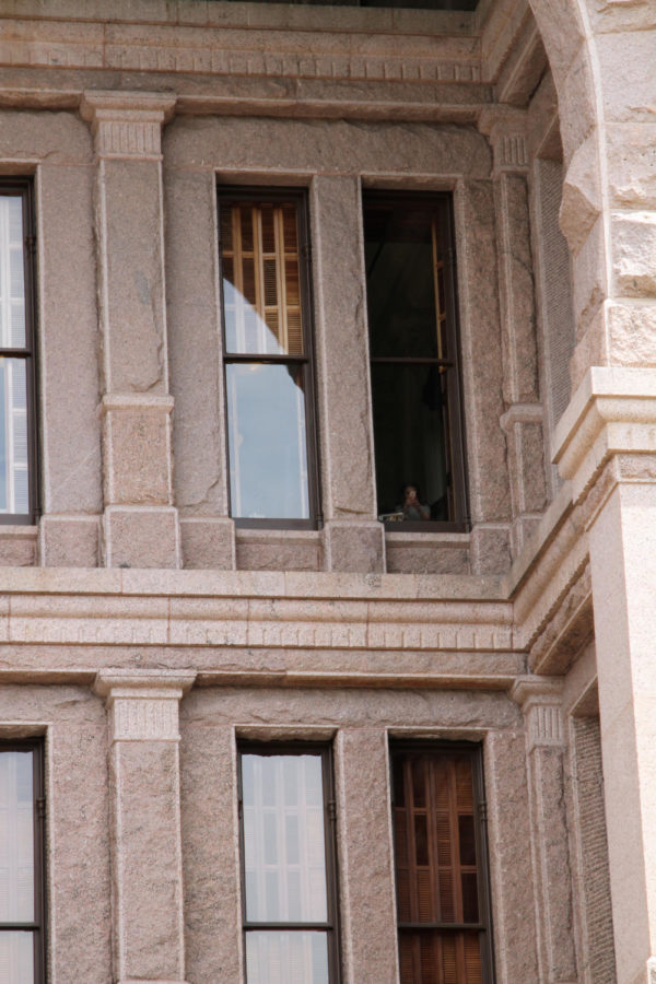 A woman films the crowd of protesters from inside the capitol building on April 20.