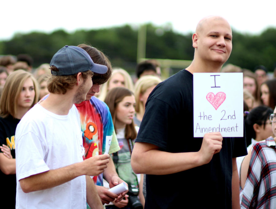 Senior Jake Caswell holds a sign opposing the walkout. He was one of several students who openly took part of the counter protest.