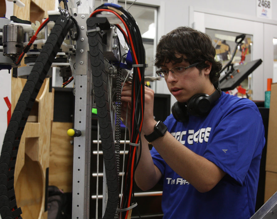 Junior Atticus Lowden tinkers with a robot in Robotics class on Feb. 21.