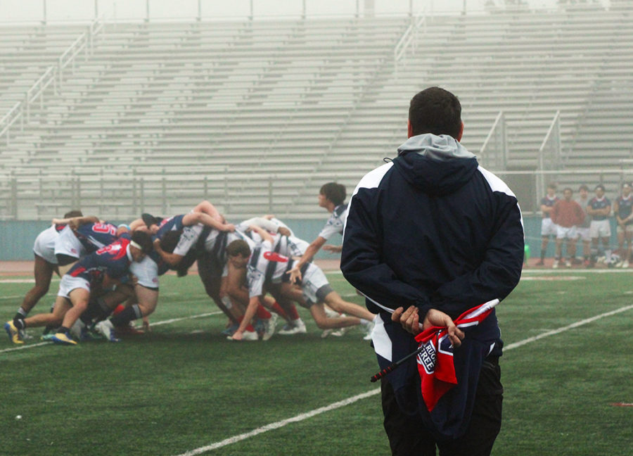 On Feb. 2nd, rugby coach Jason Andrew watches the varsity boys rugby match during the foggy morning.