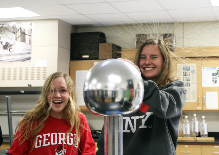 A Physics C experiment in Mr. Misages class leads to senior Carly Roses hair sticking up all around her as well as a surprised senior Chloe Harms.