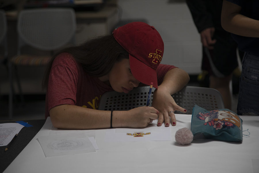 Showing of her future school's merchandise, senior Nina Guerra works on tracing the logo for the Senior Signing Day banner.