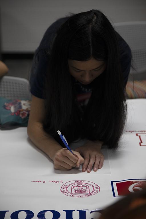 Claiming+her+spot+on+the+banner%2C+senior+Vivi+Pham+draws+her+University+of+Pennsylvania+logo+on+May+1%2C+2019.