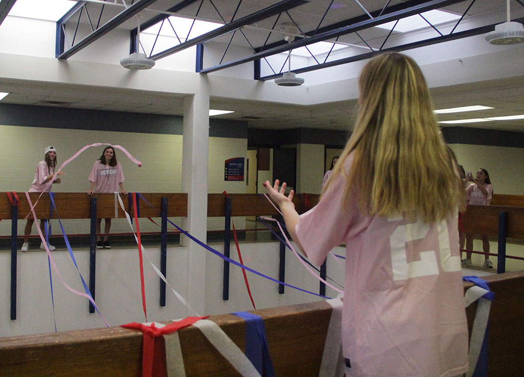Senior+Kristen+Gouchner+and+Daisy+Painter+throw+a+roll+of+streamer+at+senior+Anna+Woytko+while+decorating+the+Commons+Aug.+20.