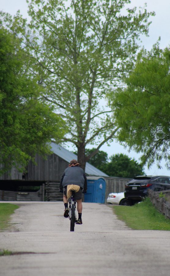 A biker rides down the road at Commons Ford Ranch April 6.  The effects of COVID-19 have made many Austin residents drawn to outdoor acitvites even more than before, as they grow more tired of being cooped up inside .