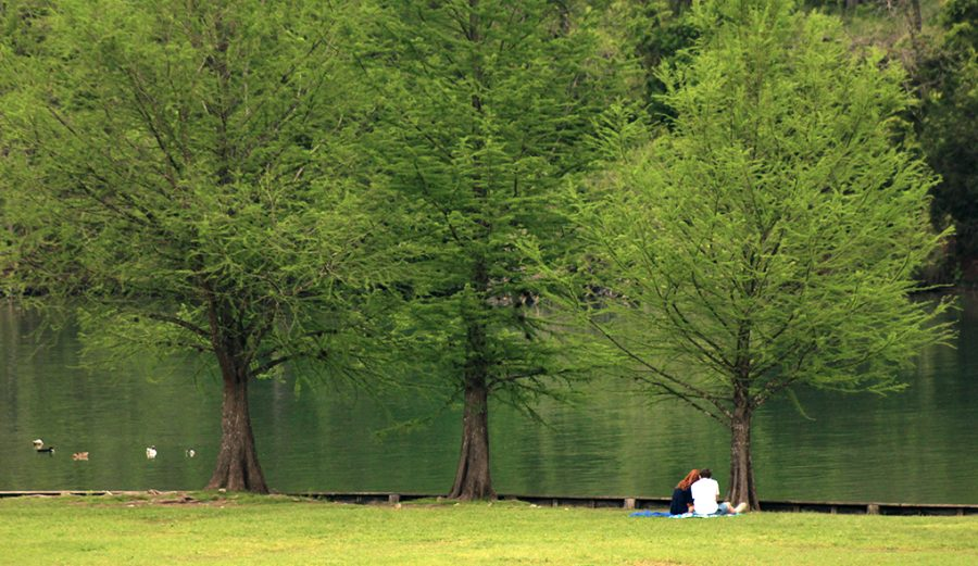 Senior couple Clark Lindesmith and Payton Shelly relax by the lake at Commons Ford Ranch April 6.