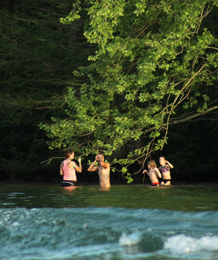 A family cools off in Lake Austin at a distance from the crowd present at Commons Ford Ranch April 10.