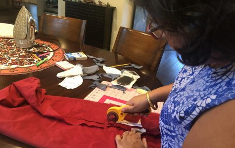 Deepika Basu Roy, mom of the writer, cuts fabric in the shape of masks using the Olson pattern before sewing them together with a sewing machine. The Olson pattern was designed by a doctor and is recommended by most medical professionals.