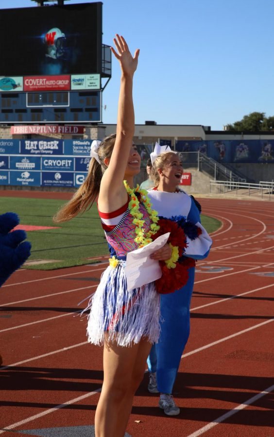 Varsity cheerleader seniors Macie Matthews and Callahan Griebel interact with the crowd of students during the pep rally Sept. 24.